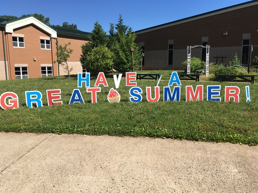 "sign outside on grass in front of school reading ""Have a great summer"""